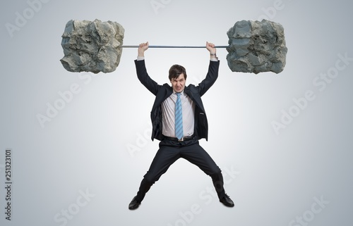 Fotografie, Obraz  Young businessman in suit is lifting heavy weights.