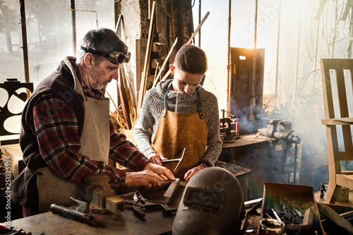 Photo A craftsman in his workshop teaches his work to his apprentice