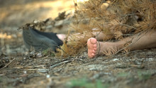 Corpse In One Shoe Covered With Tree Branch Lying On Ground, Murder In Woods