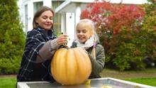 Mother And Daughter Carving Pumpkin Jack-o-lantern, Having Fun Together, Weekend