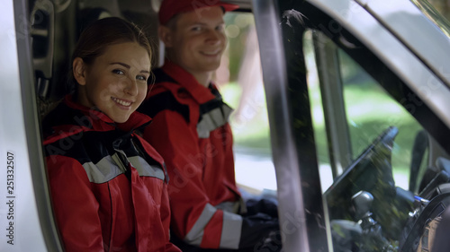 Canvas Print Ambulance crew looking into camera, sitting in transport, emergency services