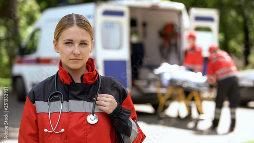Paramedic posing for camera, ambulance crew transporting patient on background Canvas Print
