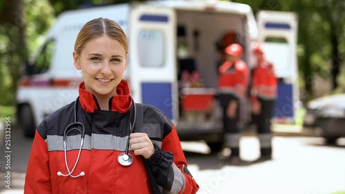 Photo Female paramedic smiling into camera, ambulance crew blurred on background