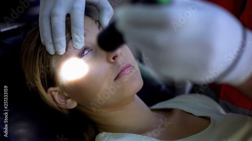 Obraz Paramedic shining light into patient eyes, testing pupil reflexes, first aid - fototapety do salonu