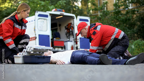 Ambulance crew helping unconscious man on road, first aid at car accident scene Canvas Print