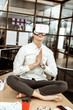 Handsome calm man practicing yoga in virtual reality