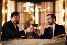 Portrait Of Two Business Partners Drinking Whiskey In Restaurant Celebrating Successful Deal, Copy Space