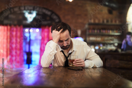 Fotografie, Obraz  Portrait of depressed man drinking alcohol alone in bar, copy space