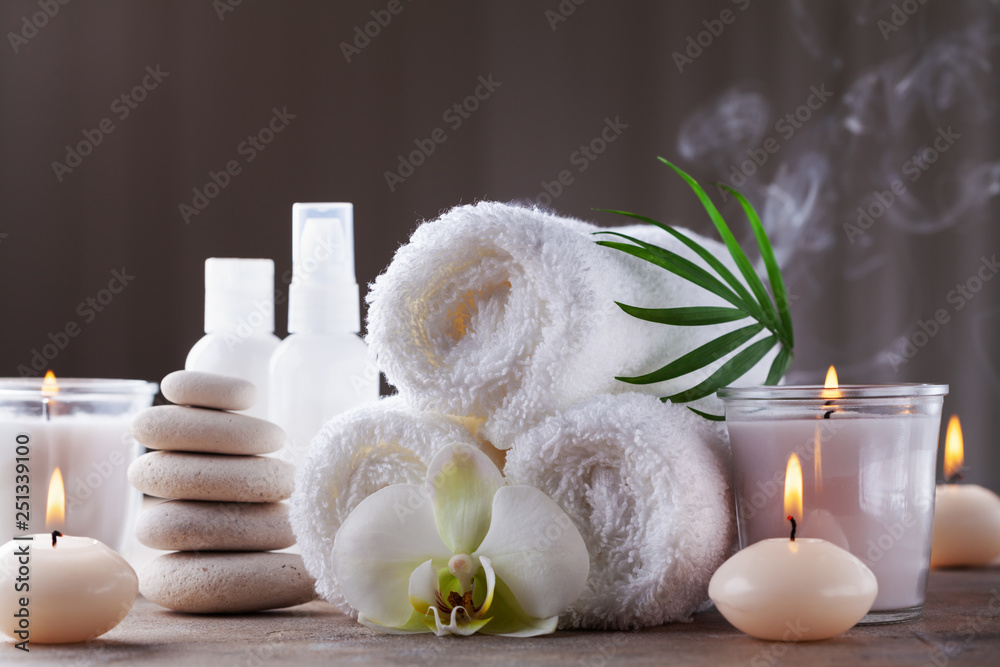 Fototapeta Aromatherapy, spa, beauty treatment and wellness background with massage pebbles, orchid flowers, towels, cosmetic products and burning candles.