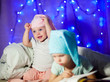 Leinwandbild Motiv kids in bed in pajamas and caps, new years eve, magic