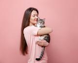 Fototapeta Zwierzęta - young attractive woman hugging cat in hands, pink background