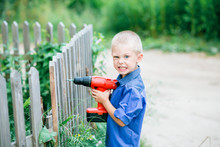 Little Blond Boy Of Five Years Old With Blue Eyes On The Street With A Screwdriver / Drill