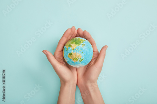 Obraz na plátne top view of woman holding planet model on turquoise background, earth day concep