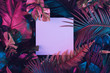 Creative fluorescent color layout made of tropical leaves with paper card note. Flat lay. Nature concept.