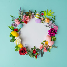 Easter Wreath Made Of Colorful Spring Flowers, Leaves And Easter Eggs. Natural Round Frame Layout With Paper Card. Flat Lay.