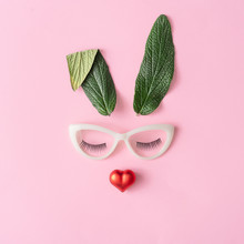 Happy Easter Minimal Concept. Bunny Rabbit Face Made Of Natural Green Leaves With Glasses And Red Heart On Pastel Pink Background. Flat Lay.