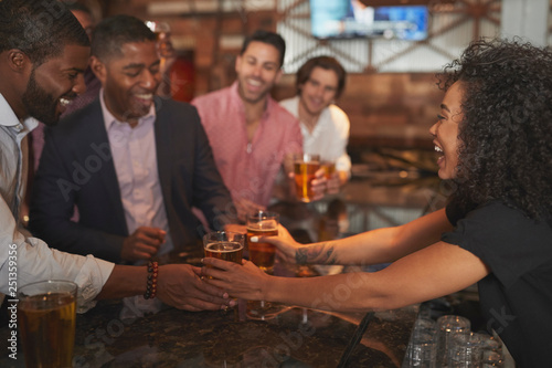 Foto op Canvas Restaurant Barmaid Serving Group Of Male Friends On Night Out For Bachelor Party Making Toast Together