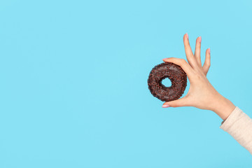 FototapetaHand holding delicious chocolate doughnut
