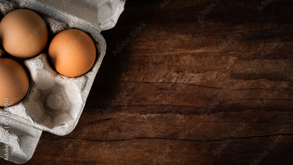 Fototapety, obrazy: Fresh brown eggs in a carton box was placed on a wooden table to prepare food. Have copyspace to enter text. In aspect ratio 16: 9. Useful for health and easy to find according to the supermarket.