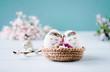 canvas print picture - Zwei süße Ostereier im Osternest mit blauem Hintergrund und Blumen dekoriert - Textfreiraum oben