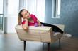 Pause beim Hantel Training, junge Frau liegt zuhause entspannt auf der Couch