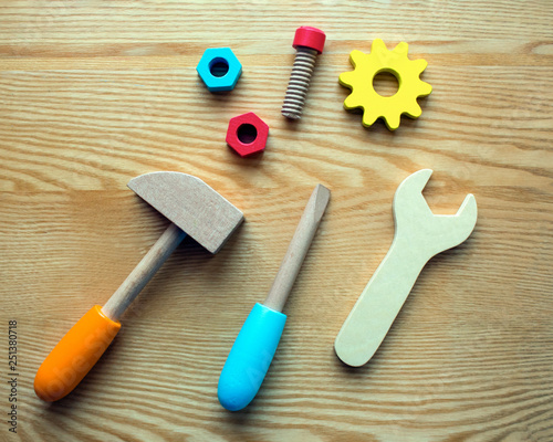 Photo set of colored wooden toy tools on a wooden background