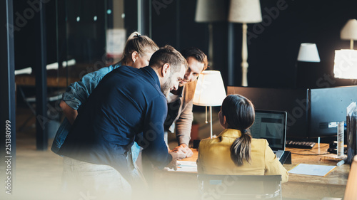 Obraz Group of young people in big office have a meeting and discussing company stats and sheets - fototapety do salonu