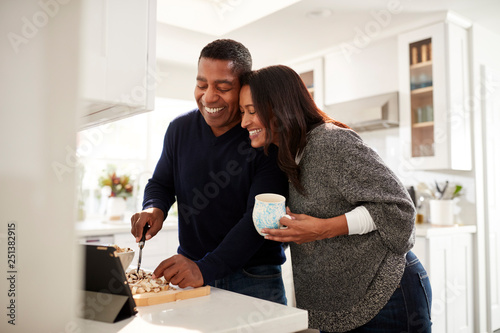 Fotografiet  Middle aged mixed race couple standing at worktop in the kitchen preparing food
