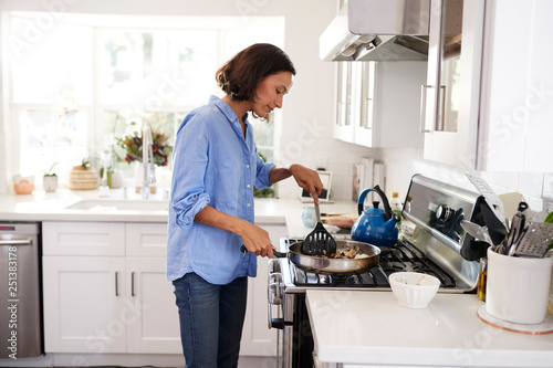 Fotografie, Obraz  Young adult woman standing at hob in the kitchen cooking food using a spatula an