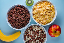Cereals Bowl Of Glazed, Chocolate Balls, Rings, Corn Flakes And Fresh Ripe Fruits For Dry Breakfast On Blue Background.