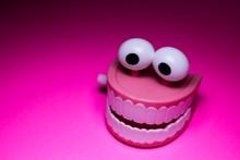 Wind Up Teeth And Eyeballs Joke Toy On Pink Background
