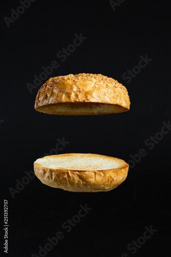 Fototapeta Floating burger buns isolated on black background. obraz