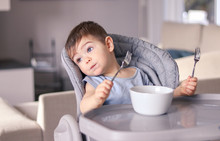 Adorable Thoughtful Funny Little Baby Boy With Smeared Face And Two Forks In Hands Tired Of Eating Leaning On High Feeding Chair Daydreaming Looking Away, Distracted From Food. Child Nutrition