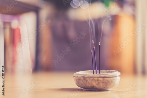Photo  Smoking and smelling joss sticks at home, feng shui; Copy space