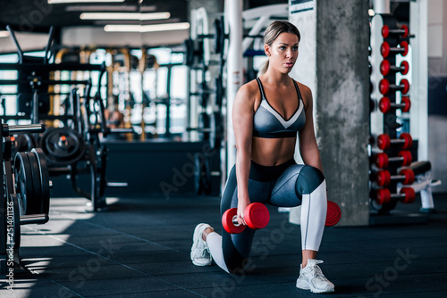 Photo Young muscular woman doing Lunges exercise with dumbbells in the gym