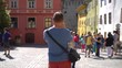 Man standing in the old town and doing photos of the architecture