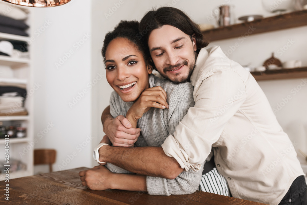 Fototapety, obrazy: Handsome man dreamily embracing beautiful african american woman. Young international couple happily spending time together in cozy kitchen at home