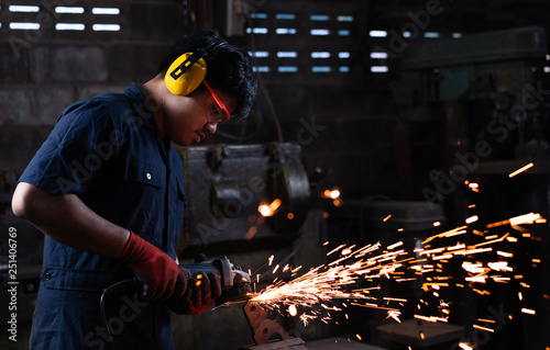 Fototapeta  Mechanical engineer worker wearing safety equipment and operating a angle grinde