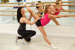 Flexible and sporty girl doing split with one leg holding on ballet barres. Female trainer holding kid and helping her to balance. They wearing sportswear, looking at camera and smiling.
