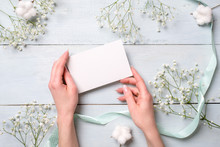 Hands Holding Blank Paper Card On Light Blue Wooden Desk With Flowers. Tender Greeting Card For Womens Or Mothers Day, Easter, Spring Holidays.