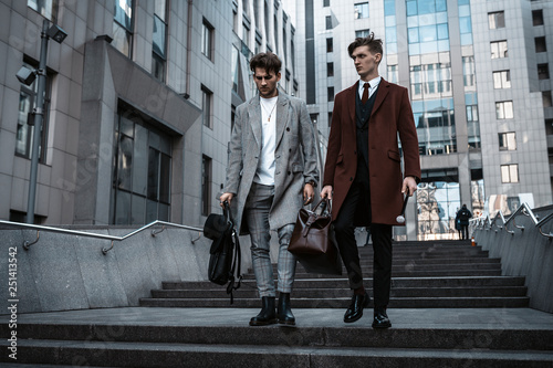 Garden Poster Milan Two fashion men models posing on city street. Wearing in classic and casual closes. Suit, coat, shirt, sweater, boots and leather bag. Men model test near business center