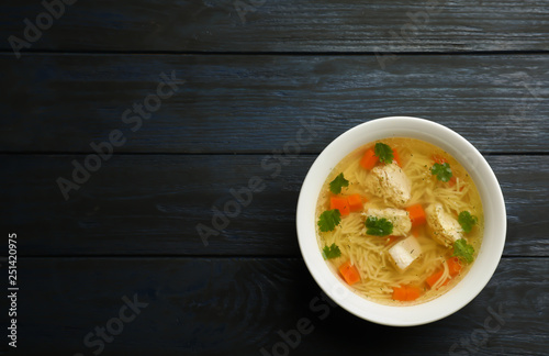 Homemade chicken soup in dish on wooden background, top view with space for text - 251420975