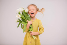 Baby Girl Blonde With A Bouquet Of Tulips On A Light Background.baby Girl Blonde Smiling.spring And Women's Day Concept.Cute Little Girl Holding White Tulips.copy Spase