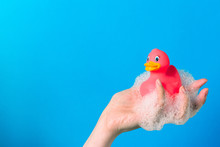 Female Hand Holding A Rubber Pink Duck In The Lather.