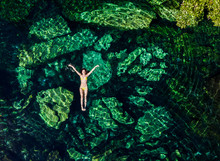 Overhead Shot Of A Attractive Young Brunette Woman In A Bikini Floating In The Cristalino Cenote Near Tulum, Mexico.