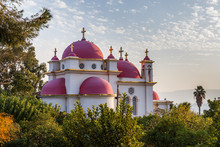 The Greek Orthodox Church Of The Holy Apostles By The Sea Of Galilee, In Capernaum, Israel. Pink Domes, Golden Crosses, White Building.