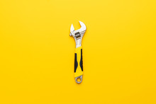 Adjustable Wrench With Yellow Handle On The Yellow Background