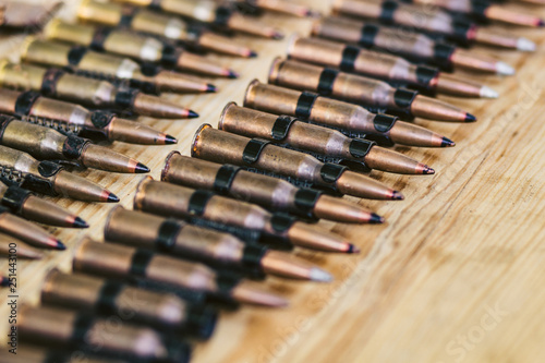 Murais de parede machine gun ammo on a wooden table, bullet belt, bandoleer, chain of ammo on wooden background,cartridge 7