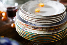Stack Of Patterned Plates With Glass Of Wine And Kumquats