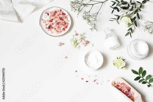 Styled beauty corner, web banner. Skin cream, tonicum bottle, dry flowers, leaves, rose and Himalayan salt. White table background. Organic cosmetics, spa concept. Empty space, flat lay, top view. - fototapety na wymiar